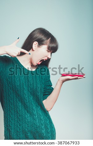 Portrait of a young woman shouting at a mobile phone, isolated on a gray background - stock photo
