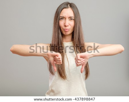 Portrait of a young woman showing thumbs down gesture over gray background - stock photo