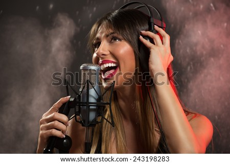 Portrait of a young woman singer with headphones in front of the microphone. Sing with mouth wide open and with an expression of happiness on her face. - stock photo