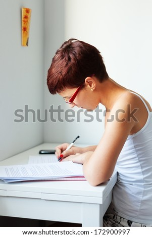 portrait of a young woman sitting at the table,learning and preparing exam  - stock photo