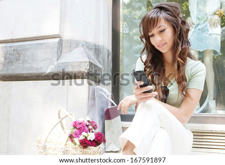 Portrait of a young woman sitting by a fashion store window display relaxing and browsing the internet using her smartphone during a shopping day out, smiling outdoors. - stock photo