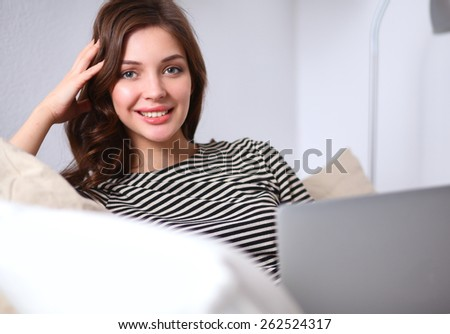 Portrait of a young woman sitting in front  her laptop on sofa - stock photo