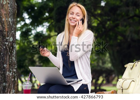 Portrait of a young woman sitting in the park  and using her credit card to make an online payment.  Online shopping everywhere - stock photo