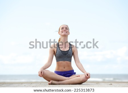 Portrait of a young woman sitting in yoga position and smiling outdoors - stock photo