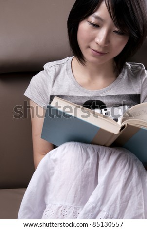 Portrait of a young woman sitting on sofa reading book - stock photo