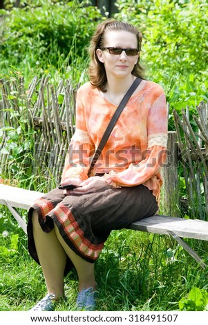 Portrait of a young woman sitting on the bench - stock photo