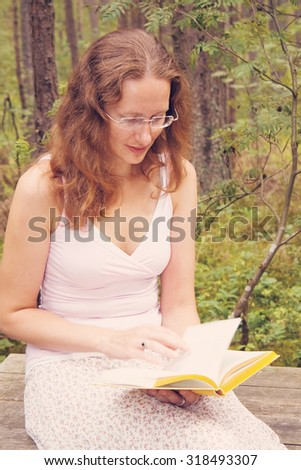 Portrait of a young woman sitting on the bench in the forest and reading a book - stock photo