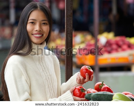 Portrait of a young woman smiling and holding vegetables at market - stock photo