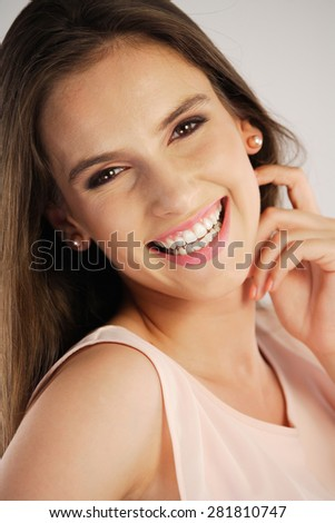 Portrait of a young woman smiling, looking over the shoulder - stock photo