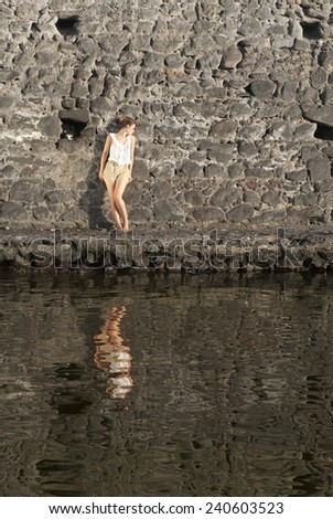 Portrait Of A Young Woman Standing Against Stonewall In Front Of Water - stock photo