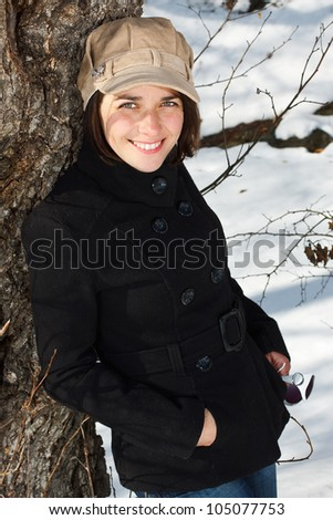 Portrait of a young woman standing in snowy winter forest, wearing a cap, black coat, jeans, white boots, standing by a tree, smiling into camera - stock photo