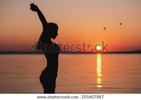 portrait of a Young woman standing on a beach and doing yoga exercises outdoor - stock photo
