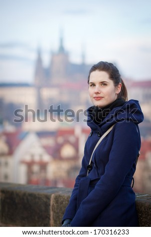 Portrait of a young woman standing on the Charles Bridge with the panorama of Prague Castle in the background (Prague, Czech Republic) - stock photo