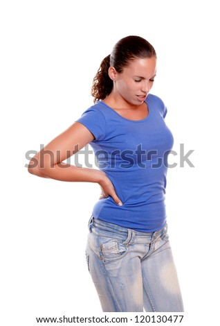 Portrait of a young woman standing with back pain against white background - stock photo