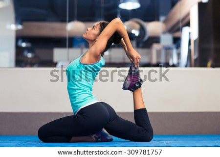 Portrait of a young woman stretching in gym - stock photo
