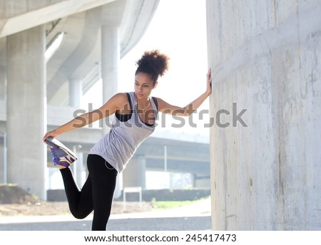 Portrait of a young woman stretching leg muscles outdoors - stock photo