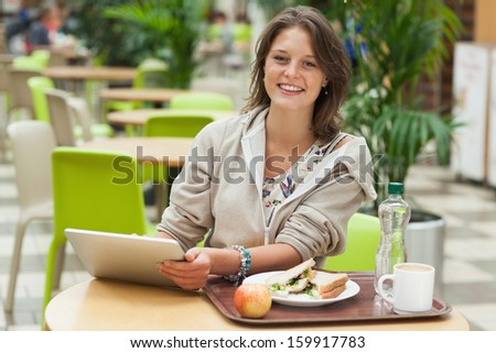 Portrait of a young woman using tablet PC while having meal in the cafeteria - stock photo