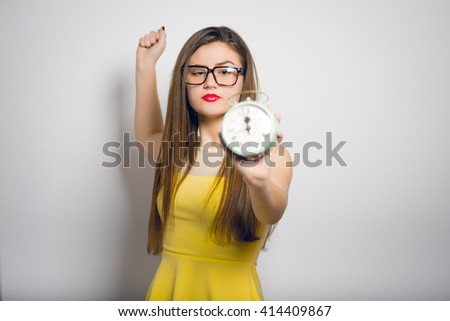Portrait of a young woman wants to break the retro alarm clock - stock photo