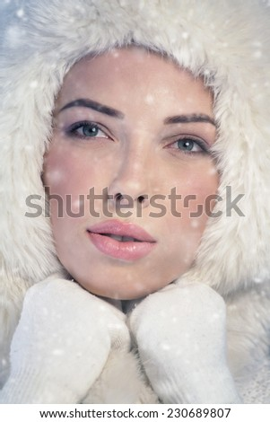 Portrait of a young woman wearing a fur cap - stock photo