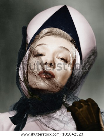 Portrait of a young woman wearing a hat and a veil - stock photo