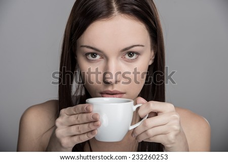 Portrait of a young woman who drinks coffee. - stock photo