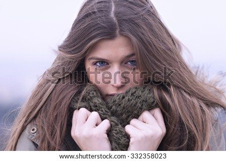 Portrait of a young woman with a scarf in winter - stock photo
