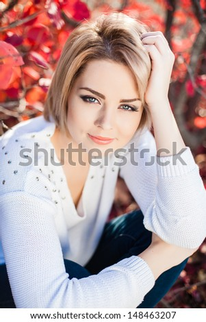 portrait of a young woman with autumn park in the background - stock photo