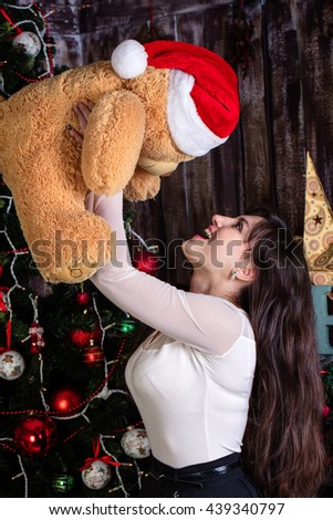 Portrait of a young woman with bear toy. Teddy bear toy in redhead Santa Claus hat. - stock photo