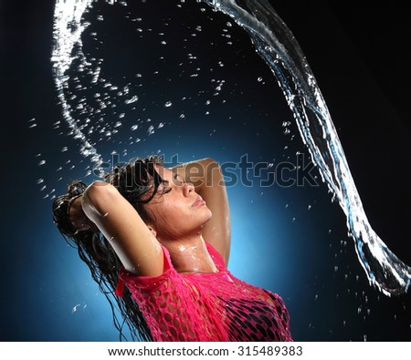 portrait of a young woman with drops of water on his face. beautiful makeup, bright emotions - stock photo