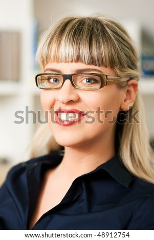 Portrait of a young woman with glasses sitting in front of a book shelf - stock photo