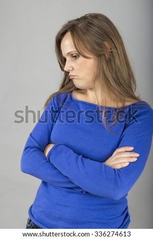 Portrait of a young woman with pouting sad expression over gray background - stock photo