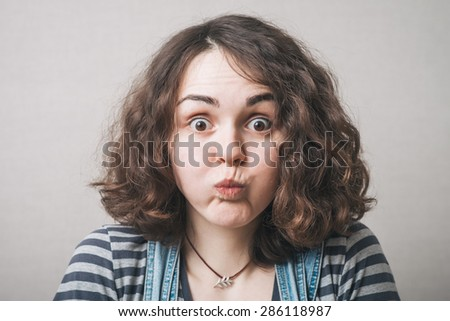 portrait of a young woman with  puffing out one's cheeks  on light grey background - stock photo