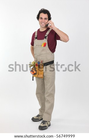 Portrait of a young worker in overalls with mobile phone on white background - stock photo