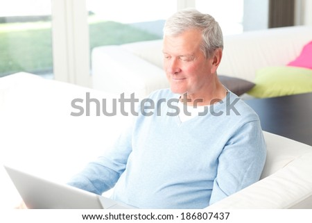 Portrait of active senior businessman sitting and working on computer. Small business.  - stock photo