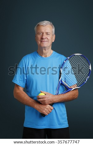 Portrait of active senior tennis coach standing against isolated background while holding in hands a tennis racket and tennis ball. - stock photo
