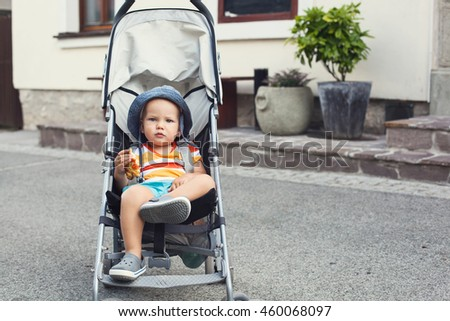 Portrait of adorable a child in a stroller on the street. Bled, Slovenia. European streets, summer atmosphere, leisure and travel. - stock photo