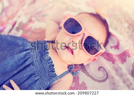 Portrait of adorable baby girl wearing sun glasses, vintage style warm color tone - stock photo