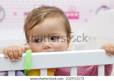 Portrait of adorable baby in the crib. - stock photo