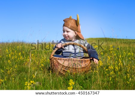 portrait of adorable baby toddler sitting in picnic basket on rural field with flowers in south sweden - stock photo