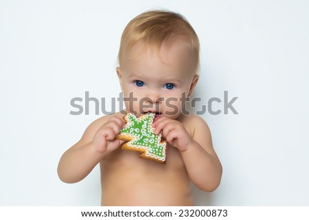 portrait of adorable beautiful funny emotions baby girl eating cookie of christmas tree form - stock photo