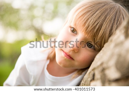 Portrait of adorable blond kid boy looking into the distance and thinking. Serious child dreaming while sitting outdoors.  - stock photo