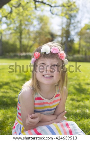 portrait of adorable blond young girl in preschool age wearing flowers in hairs outdoors - stock photo
