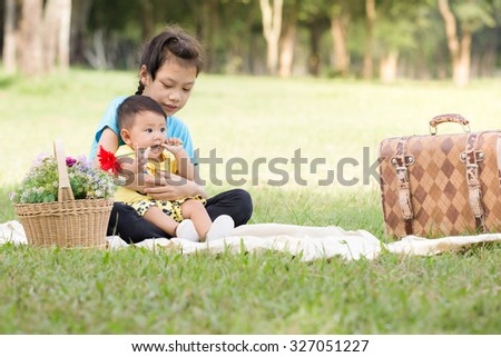 Portrait of adorable brother and sister smile and  hugging sitting in park. - stock photo