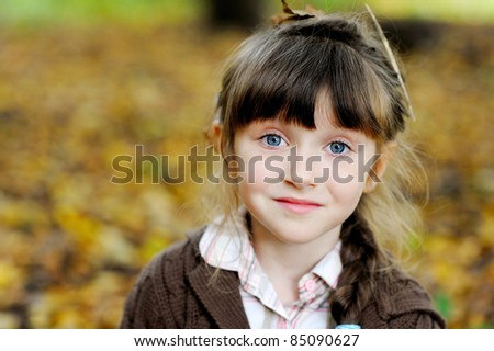 Portrait of adorable child girl with blue eyes in autumn forest - stock photo