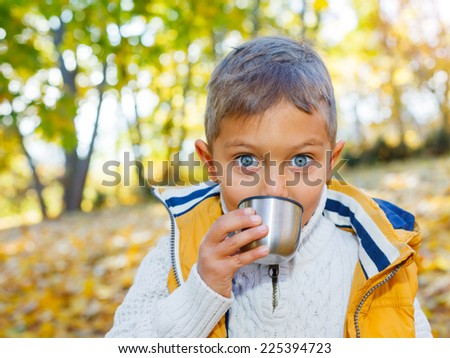 Portrait of Adorable cute boy resting and drinking tea from a thermos in the beauty autumn park  - stock photo