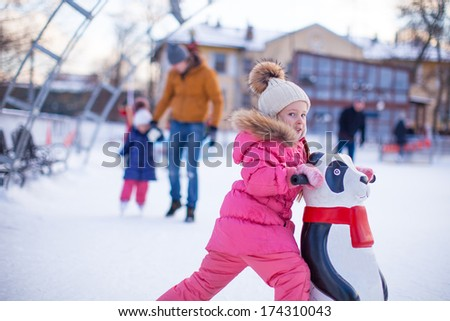 Portrait of adorable girl skating on the ice-rink background her father and little sister - stock photo