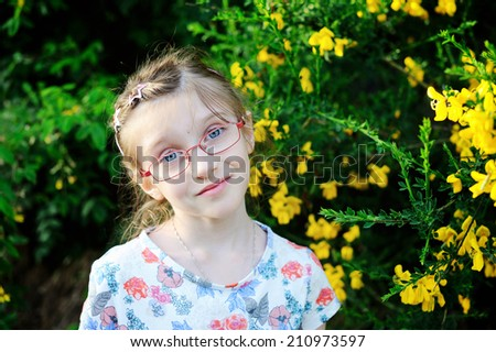 Portrait of adorable kid girl in the glasses near the yellow flowers - stock photo