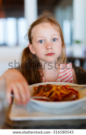 Portrait of adorable little girl eating spaghetti for a lunch at restaurant - stock photo