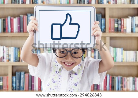 Portrait of adorable little girl holding a digital tablet and showing a thumb up sign on the tablet screen - stock photo