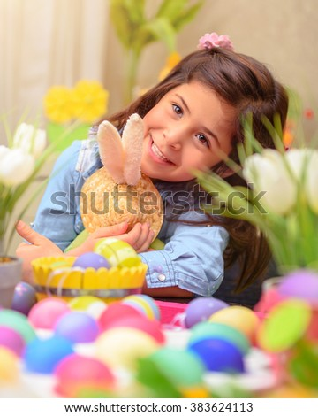 Portrait of adorable little girl with pleasure hugging her friend, soft toy Easter bunny, having fun at home in happy holiday day - stock photo